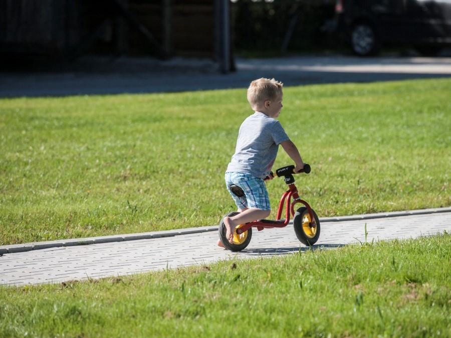 Kinderen gebruiken het erf als fietsparcour